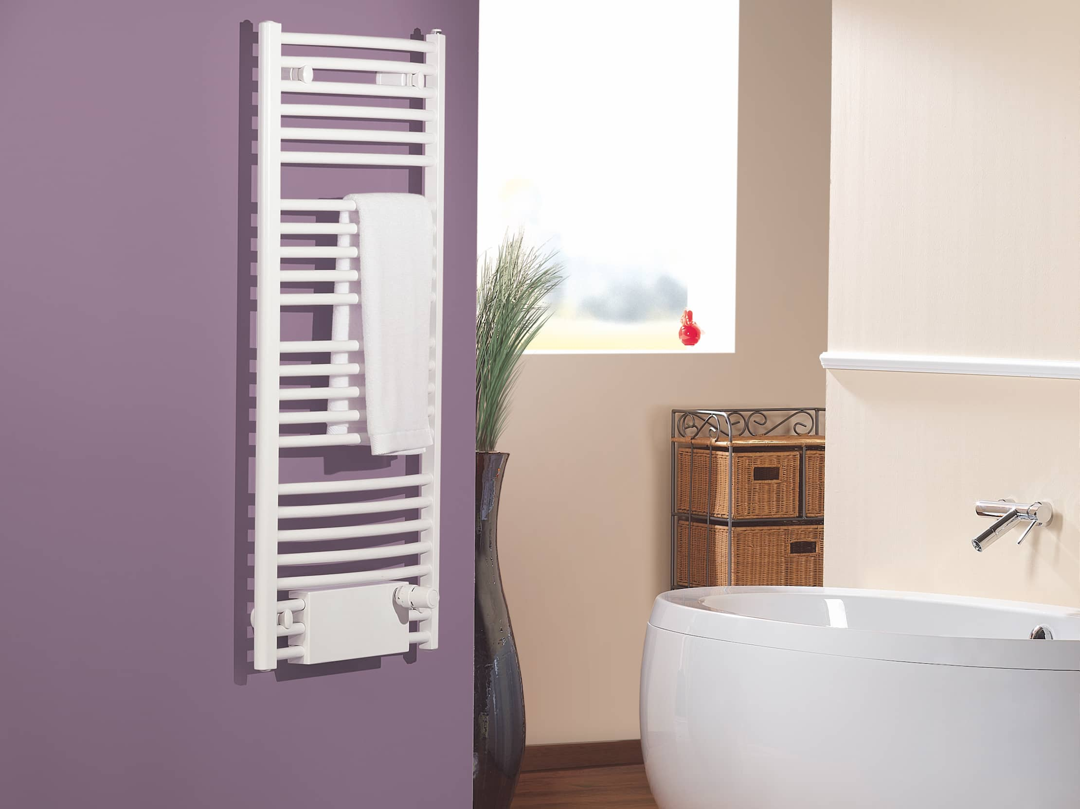 The white towel radiator, mounted on purple wall in the bathroom of a house.